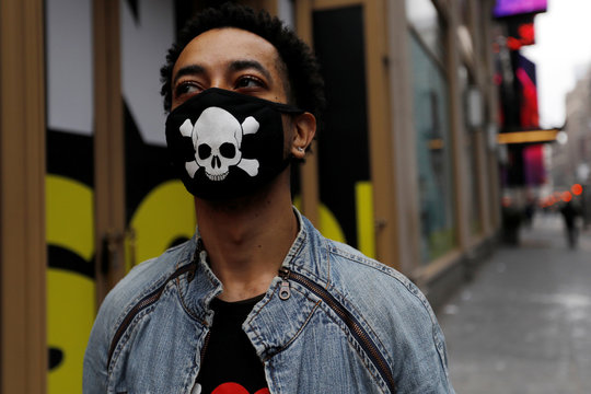 A man wears a protective mask decorated with skull and crossbones design as he walks in midtown Manhattan during the coronavirus outbreak in New York