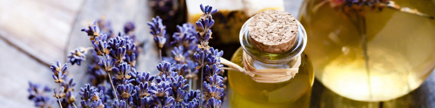 Concept of natural organic oil in cosmetology. Moisturizing skin care and aromatherapy. Gentle body treatment. Handmade soap. Atmosphere of harmony relax. Wooden background, lavender flower. Banner