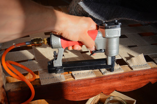 Making new upholstery on old restored furniture. Woman work with pneumatic stapler in upholstery workshop. Furniture straps.