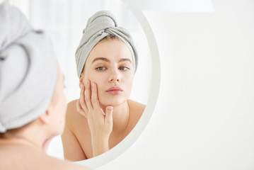 Obraz Portrait of  young girl with  towel on head in white bathroom looks and touches her face in the mirror and enjoys youth and hydration. Natural beauty, home care for problem skin - fototapety do salonu