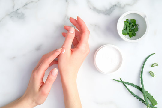 Cosmetic cream on female hands, jar with aloe vera cream and green sliced stems on marble background. Woman applying organic moisturizer hand cream. Hand skin care concept