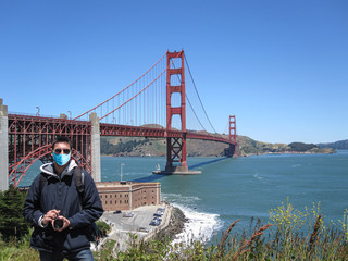 Man wearing surgical mask in San Francisco, with the Golden Gate on the Background. Concepts of coronavirus, Self-isolation, quarantine and California's stay-at-home order