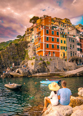 Fototapeten Ligurien Riomaggiore Cinque Terre Italy , colorful village harbor front by the ocean, young couple watching sunset