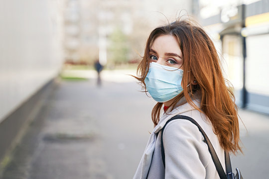 Young woman with beautiful blue eyes and disheveled hair wearing protection face mask against coronavirus MERS-Cov, Novel coronavirus 2019-nCoV. Concept of coronavirus quarantine and pandemic.