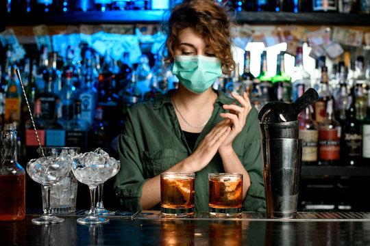bartender girl in medical mask at bar counter.