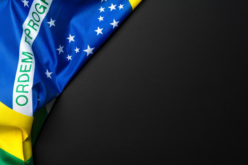 Brazilian flag lying on black grainy background