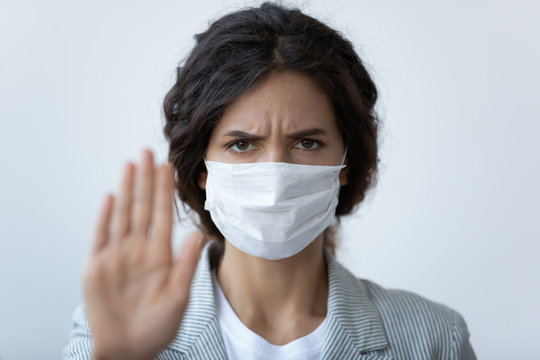Head shot angry woman in mask stretched arm as sign of stop COVID-19 follow quarantine rules, stay at home, avoid physical contact, wash hands keep distance, prevent spread of epidemic disease concept