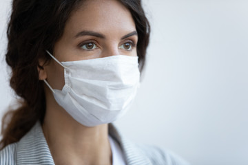 Close up image woman in facial medical mask on blue background, concept of protection to globally...