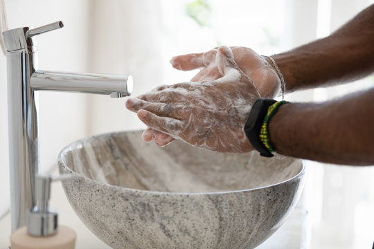 Close up african man cleans hands with soap in bathroom. Anti bacterial agent sanitizer that contains alcohol kill microbe and bacteria, safety precautions against COVID-19, personal hygiene concept
