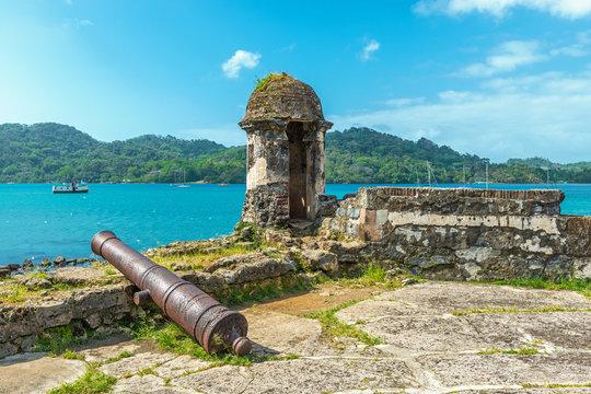 Old Spanish cannon at the fortress ruin of Santiago with a view over the Caribbean Sea in Portobelo near Colon, Panama, Central America.