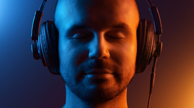 Young man in headphones enjoys the music. His eyes are closed. Two-tone lighting