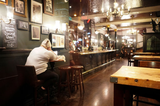 A woman sits alone in a pub, on the day Prime Minister Boris Johnson ordered all pubs to close in response to the number of the coronavirus disease (COVID-19) cases continuing to grow, in London