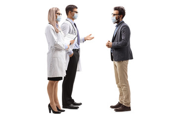 Male and female doctors wearing protective medical masks and talking to a man with a medical face...