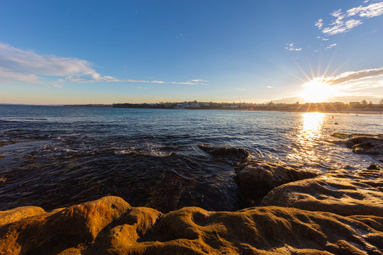 Rocky shoreline around Bondi beach, Sydney, Australia. Sunset near the famous surfer beach. Sunset over the pacific ocean. Sun reflecting in the smooth water. Breathtaking colorful sea side sunset.