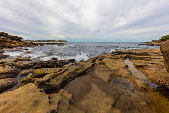 The rocky shoreline around Bondi beach, Sydney, Australia. Waves splashing at the rocks in the water. White clouds on blue sky. The cliffs beside the sandy beach. A paradise for surfers