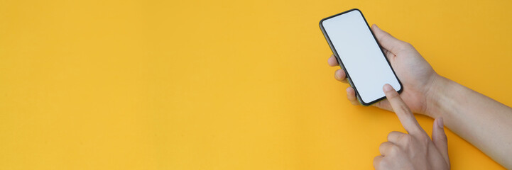 Cropped shot of a man touching on blank screen smartphone on yellow background