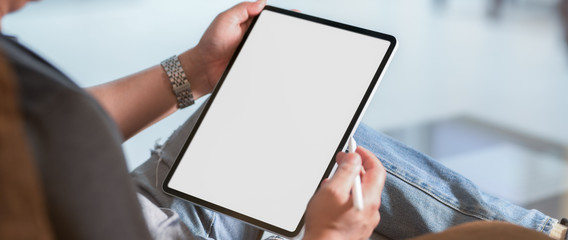 Cropped shot of a man sitting at modern living room and using vertical blank screen tablet Fotobehang