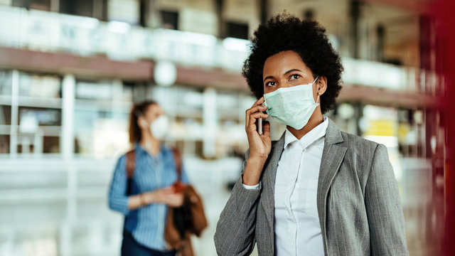 African American businesswoman wearing protective mask while making a phone call at the airport.