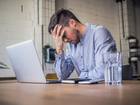 worried and disappointed remote online working man in casual outfit with laptop sitting in an coworking / home office at a work desk