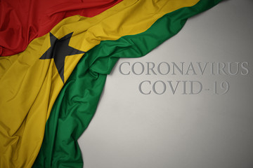 waving national flag of ghana on a gray background with text coronavirus covid-19 . concept.