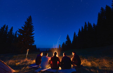 Poster Camping Summer camping under stars. Rear view of group of five hikers, men and woman sitting near bright bonfire, tourist tent under dark night sky with sparkling stars. Concept of tourism, night camping.