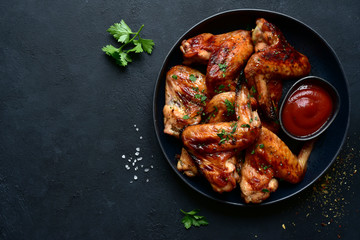 Grilled spicy chicken wings with ketchup. Top view with copy space.