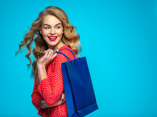 Cheerful  young woman holds bags with a purchases. Joyful trendy girl with a colorful shopping bags. Model in a red shirt over blue background holding bags with gifts. Happy caucasian woman.