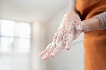 Asian woman use soap to wash your hands in the bathroom to get rid of the virus.