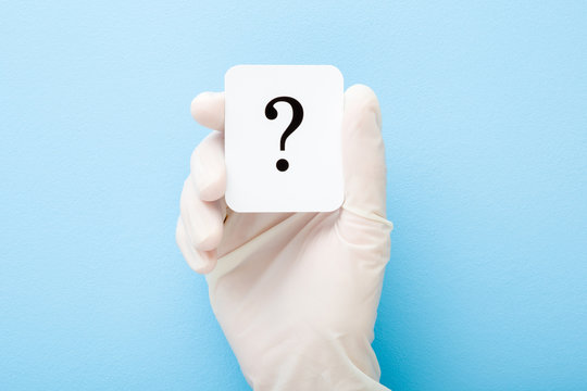 Doctor hand in white rubber protective glove showing question mark. Light blue background. Concept of medical issues. Closeup. Top down view.