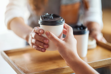 A waitress holding and serving paper cups of hot coffee to customer in cafe