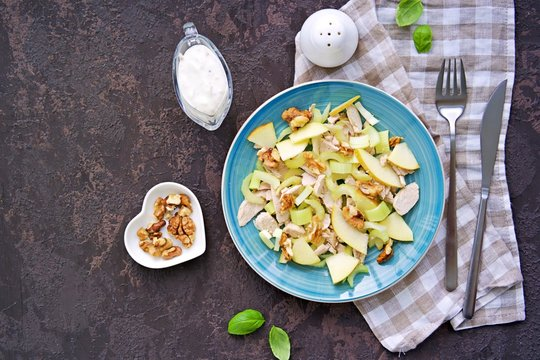 A healthy salad of stem celery, apples, boiled turkey or chicken and walnuts on a blue plate on a dark concrete background. Recipes of vegetable salads. Diet, detox. Top view. Copy space.
