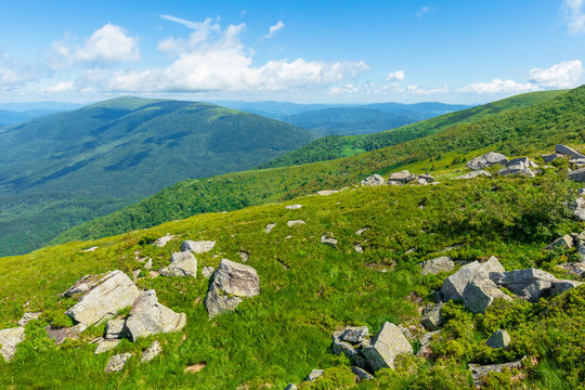 rocks on the alpine hillside meadow. beautiful summer nature scenery. green grass on the hills and fluffy clouds on the blue sky. great mountain landscape of carpathians