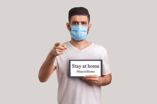 #StayAtHome. Man in protective mask holding Stay at home inscription and pointing to camera, warning of coronavirus quarantine, Covid-19 epidemic, preventive measures for spread of infectious disease.