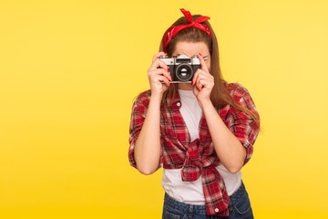 Portrait of pinup girl in checkered shirt and headband taking picture with old fashioned camera, traveler making photo