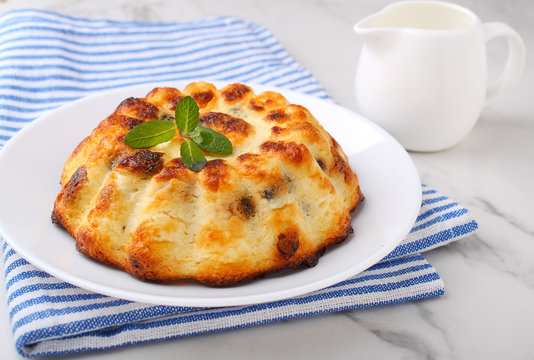 Cottage cheese casserole decorated with mint on a marble background