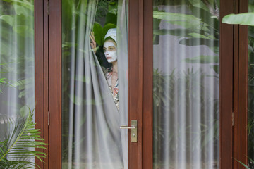 Young woman with hair wrapped in towel and facial beauty mask looking outside through window. Bored and completely alone at home. Coronavirus outbreak and self-quarantining concept.