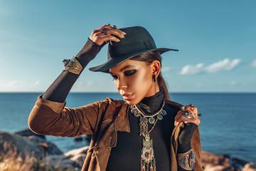 beautiful young fashionable woman portrait wearing hat at sunset