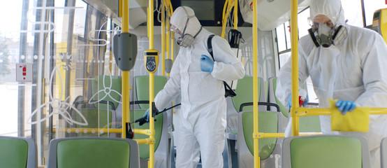 HazMat team in protective suits decontaminating public transport, bus interior during virus outbreak
