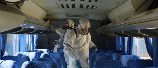 HazMat team in protective suits decontaminating public transport tourist bus interior during virus outbreak