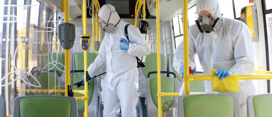 HazMat team in protective suits decontaminating public transport, bus interior during virus outbreak