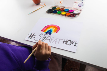 Child painting rainbow of hope, stay at home