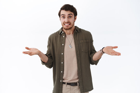 Oops my bad, sorry didnt know. Awkward cute hipster guy saying yikes shrugging and throwing hands indecisive, cant tell, apologizing being guilty, embarrassed for silly mistake, white background