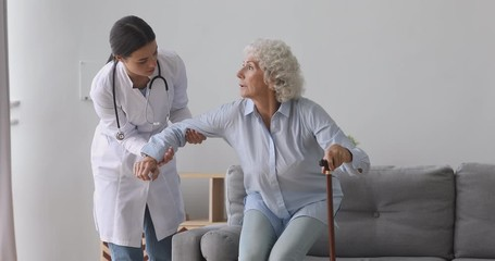 Fototapete - Caring young nurse in uniform helping old disabled hoary woman getting up from couch. Kind female doctor caregiver providing medical service to unhealthy elderly lady patient in retirement house.