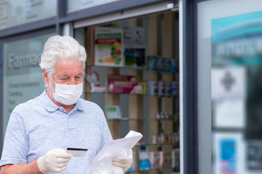 Elderly man with mask and protective gloves leaves the pharmacy with medicines and instructions. Fear of coronavirus infection, covid-19. Concept of retired senior and fear of contagion