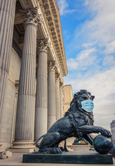 Bronze lion statue in front of the Spanish Parliament wearing a face mask as a symbol of the Madrid and Spain lockdown caused by coronavirus outbreak..