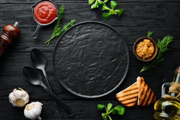 Fotomurales - Black kitchen background with spices and plate. Top view. Free space for your text. Rustic style.