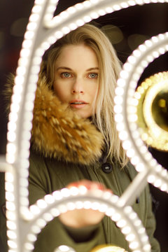 Blonde in jacket in front of burning garland on blurry background