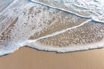 olas ronmpiendo en la arena de la playa