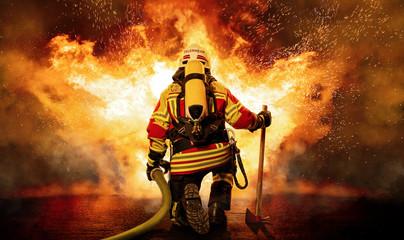 Fototapeta Feuerwehrmann kniet vor einem Feuer obraz