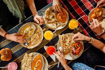 Foto op Canvas Kruidenierswinkel people eating indian meal, top view, hands